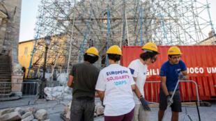 De jeunes volontaires actifs dans la reconstruction d'édifices à Norcia en Italie.