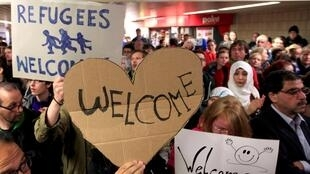 Wellwishers welcome migrants at the main railway station in Dortmund, Germany