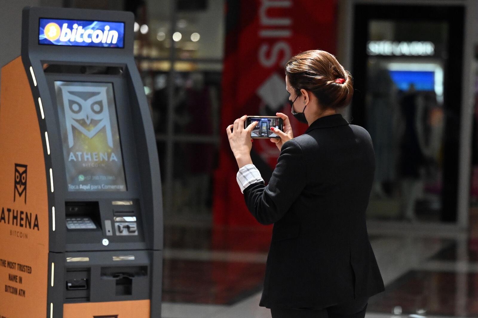Una mujer toma una foto de un cajero automático de Bitcoin, luego de su inauguración por parte de Athena Bitcoin Inc. en un centro comercial de San Salvador, el 24 de junio de 2021.A partir de septiembre, el bitcoin operará como moneda de curso legal  en El Salvador.