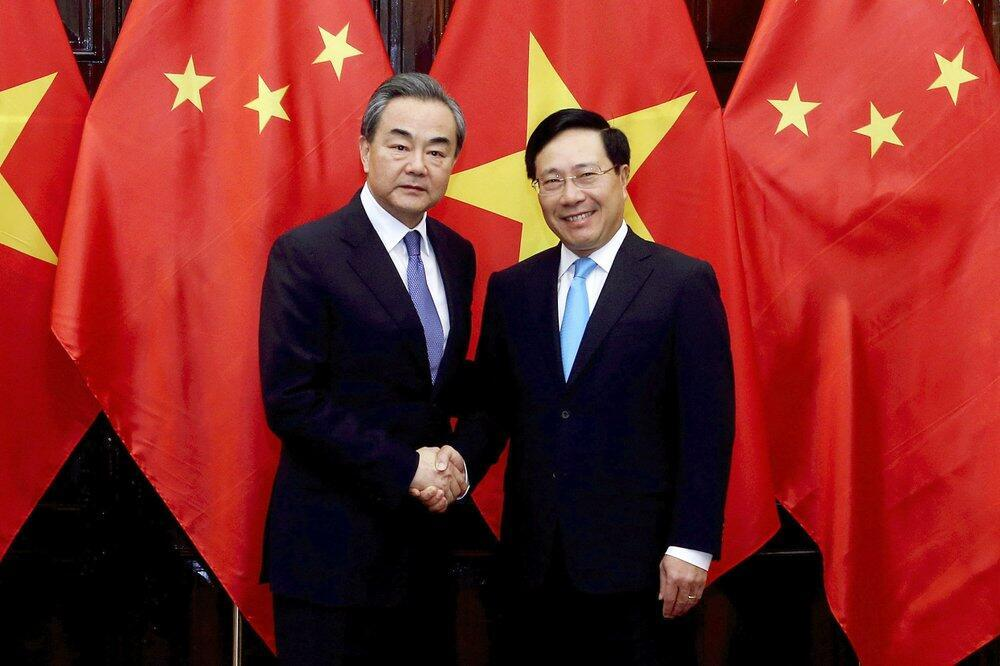 Chinese Foreign Minister Wang Yi, left and Vietnamese Foreign Minister Pham Binh Minh shake hands in Hanoi, Vietnam, Sunday, April 1, 2018. Wang Yi is on a three-day visit to Vietnam to attend a Greater Mekong Summit and hold talks with Vietnamese leaders to boost the bilateral relation. (AP Photo)