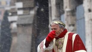 A man dressed as Roman emperor Julius Caesar during a snowstorm in front of the Colosseum in Rome