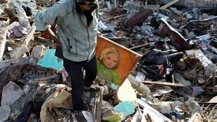 Agus Fardhan carries a portrait of his mother after he found it at her destroyed home, in Palu, Central Sulawesi, Indonesia, October 7, 2018.