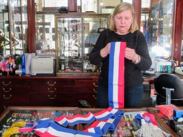 Sylvie Keller, manager of Maison Bacqueville, unrolls a mayor sash, which is 1.9 metres long.