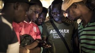 Des Guinéens suivent la publication des premiers résultats provisoires partiels de l'élection présidentielle, le 20 octobre 2020.