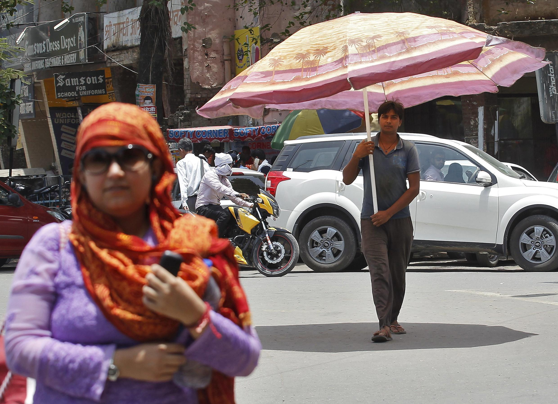 Le 29 mai 2015 à Allahabad, un homme marche avec un parasol pour se protéger du soleil et de la chaleur excessive qui frappe le sud de l'Inde.