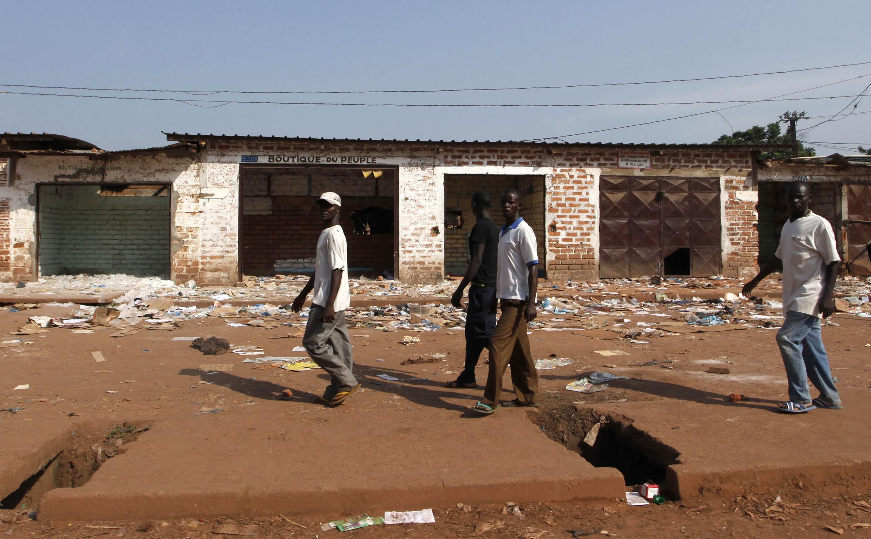 Des hommes passent devant des magasins fermés d'un quartier musulman de Bangui, Centrafrique, le 12 décembre 2013.
