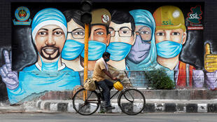 A mural praises the anti-epidemic medical workers in Covid-19 in the Indian capital New Delhi as a man passes by on a bicycle.
