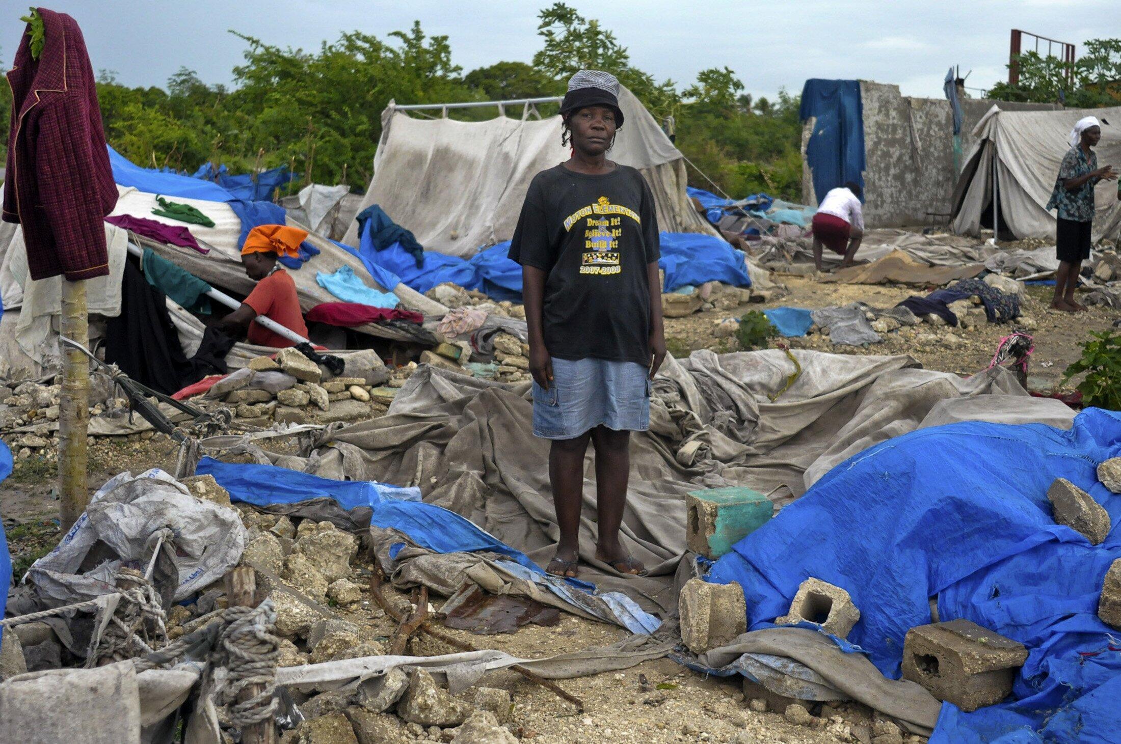 Haitiana mostra local onde morava desde o terremoto de 2010 até a destruição de sua barraca pela tempestade Isaac.