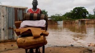 Un homme transporte ses affaire dans une brouette dans le quartier de Kirkissoye à Niamey, après la crue du fleuve Niger, le 27 août 2020.