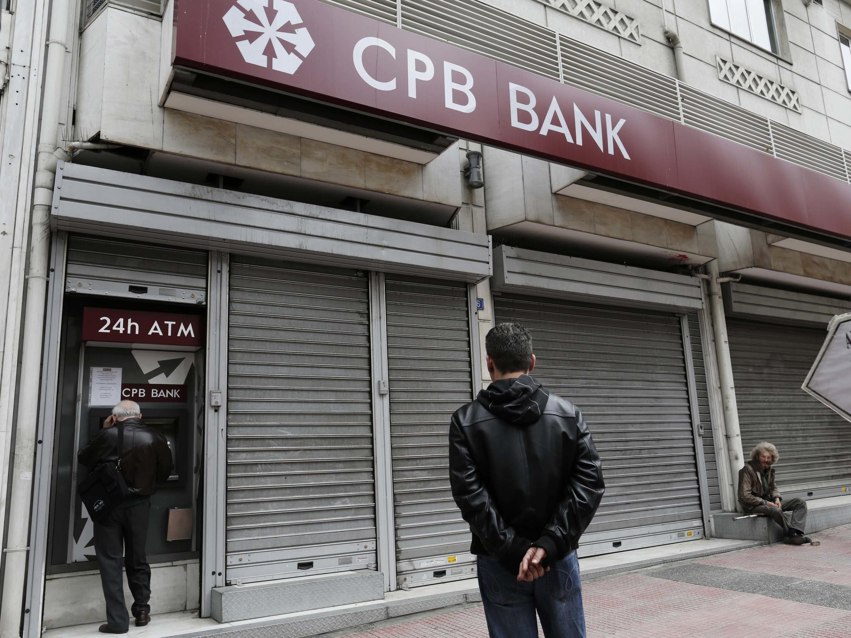 Des clients de la Cyprus Popular Bank retirent de l'argent dans une agence à Athènes, le 21 mars 2013.