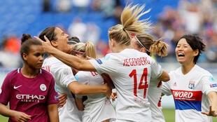 Lyon's Lucy Bronze celebrates scoring their first goal with teammates.