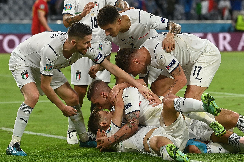 La joie du milieu de terrain italien Nicolo Barella (g), félicité par ses coéquipiers, après avoir ouvert le score face à la Belgique, en quart de finale de l'Euro 2020, le 2 juillet 2021 à Munich