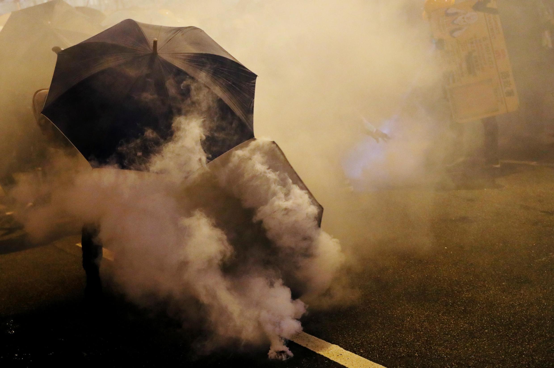 Militantes pró-democracia utilizam guarda-chuvas para se proteger das bombas de gás lacrimogêneo em Hong Kong, 28 de julho de 2019.