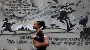 Une femme marchant devant un mur de graffiti, à Nairobi, capitale du Kenya, le 23 octobre 2017. (Photo d'illustration)