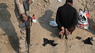 Soldado iraquiano posa ao lado de integrante do grupo Estado Islâmico que teria participado des massacres nesta semana.