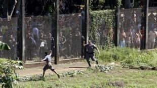 Un policier tente d'arrêter un prisonnier passé par dessus la cloture le 30 novembre 2015 après une mutinerie dans la prison d'Escuintla au Guatemala.