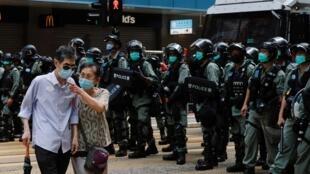 Une couple passe devant une rangée de policiers à Hong Kong, le jour de l'anniversaire de la rétrocession du territoire à la Chine, le 1er juillet 2020.