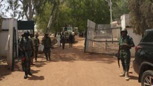 Soldados y policías nigerianos montan guardia a la entrada del Colegio Federal de Mecanización Forestal en Mando, estado de Kaduna, noroeste de Nigeria, el 12 de marzo de 2021, después de que una banda de secuestradores irrumpiera en la escuela disparando indiscriminadamente y se llevara a alumnos de rehenes, el 12 de marzo de 2021.
