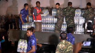 La police distribue des bouteilles d'eau à la population depuis le 4 décembre, comme ici à Malé, capitale des Maldives.