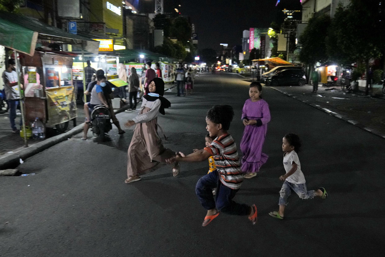 Des enfants jouent au milieu d'une rue de Jakarta fermée à cause des restrictions dues à la propagation du variant Delta du Covid-19, le 21 juin 2021.