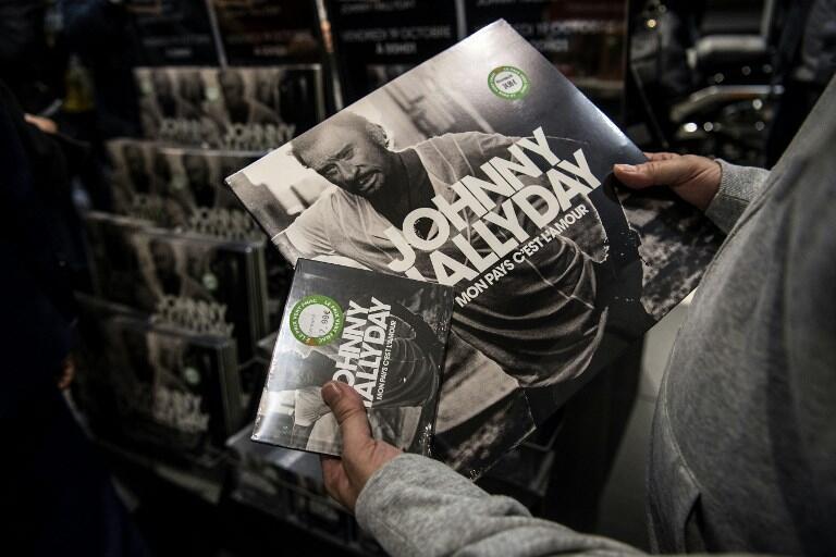 Um fã segura o álbum póstumo de Johnny Hallyday, em CD e em vinil.
