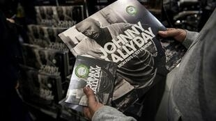 Un fan porta entre sus manos el album postumo de Johnny Hallyday, en CD y en vinilo.