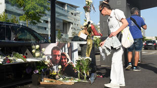 A woman lays flowers at the bus stop where bus driver Philippe Monguillot was savagely beaten for refusing to let aboard a group of people who were not wearing face masks, Bayonne, France, 8 July 2020.