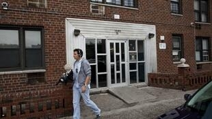 Un journaliste passe devant l'immeuble où vit Nafissatou Diallo, la victime présumée de DSK, le 18 mai 2011.