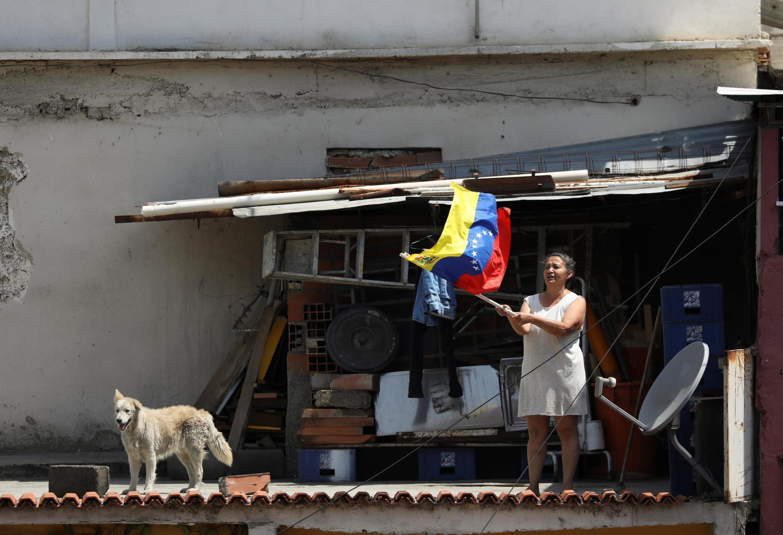 Une femme brandit un drapeau vénézuélien lors d'une procession religieuse dans le bidonville d'Antimano malgré une quarantaine à l'échelle nationale en raison de l'épidémie de Covid-19 à Caracas, le 8 avril 2020.