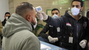 Autoridades sanitárias controlam temperatura de passageiros no aeroporto internacional do Cairo.