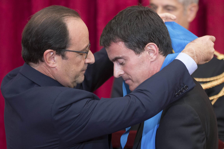 French President François Hollande awards Prime minister Manuel Valls with the Grande Croix de l'Ordre National du Merite, 22 October 2014.