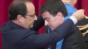 French President François Hollande awards Prime minister Manuel Valls with the Grande Croix de l'Ordre National du Merite, 22 October 2014.