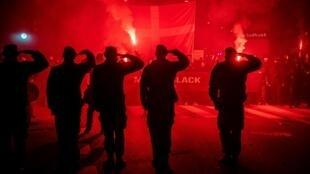 """Manifestantes saludan mientras participan en una marcha organizada por el movimiento antirrestricción """"Hombres de Negro"""" en Copenhague, Dinamarca, el 10 de abril de 2021"""