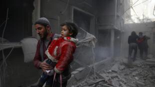 Un hombre huye de los bombardeos aéreos con una niña, en Duma, Guta Oriental, Siria.