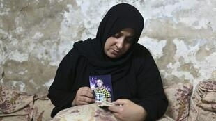 The mother of Ehab Abu Nada, 18, holds a photograph of her son as she reads the Koran. The young man died after setting himself on fire in the Gaza Strip, apparently in protest at economic hardship in the Palestinian enclave.