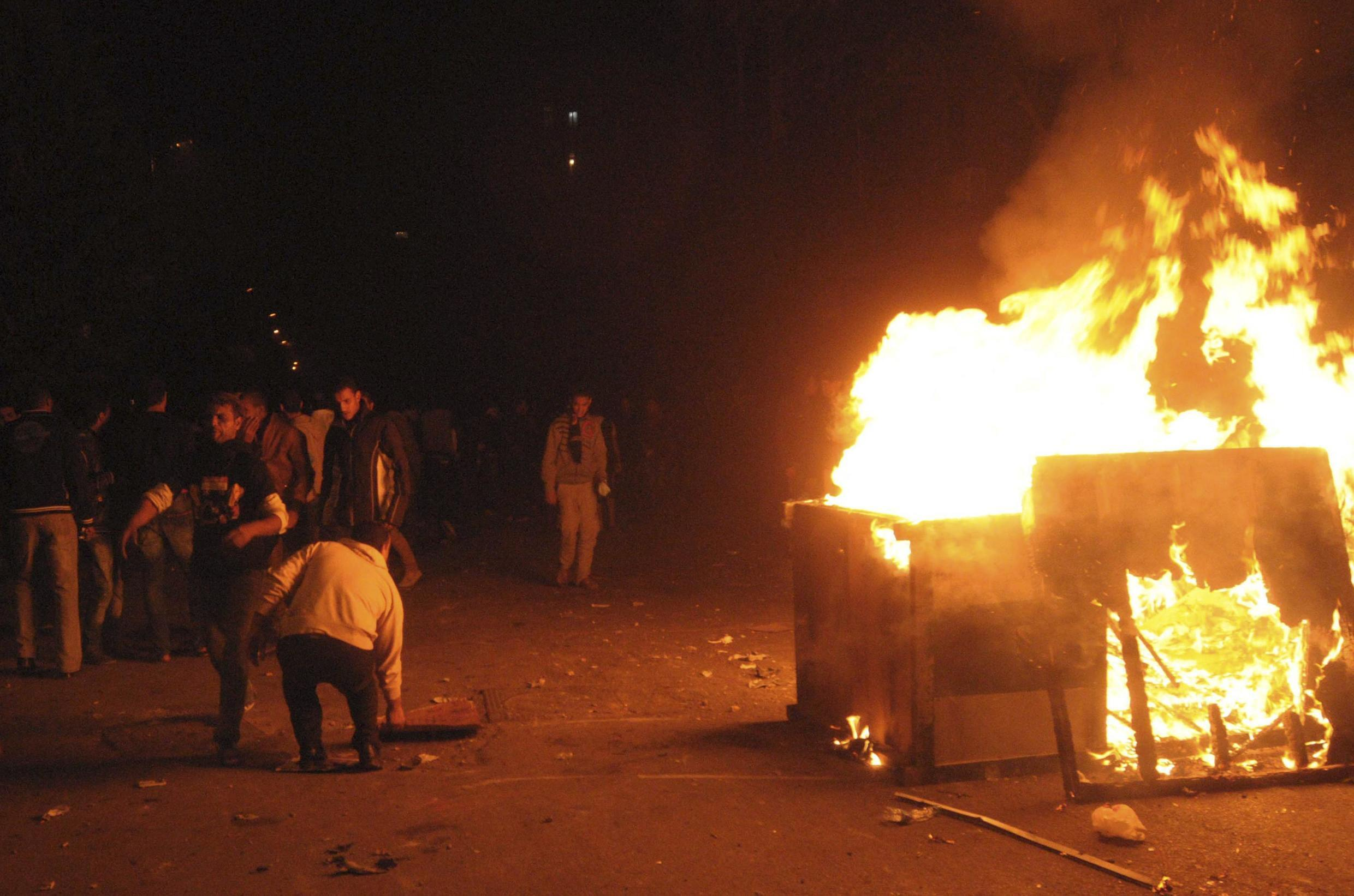 Demonstrators burn banners and police boxes on Tahrir Square on Saturday night
