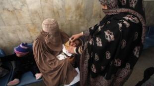 Une femme vaccine un enfant contre le virus de la poliomyélite, le 19 décembre 2012, à Peshawar.