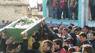 Anti-government protesters carry the coffin during funeral in Hula near Homs on Monday