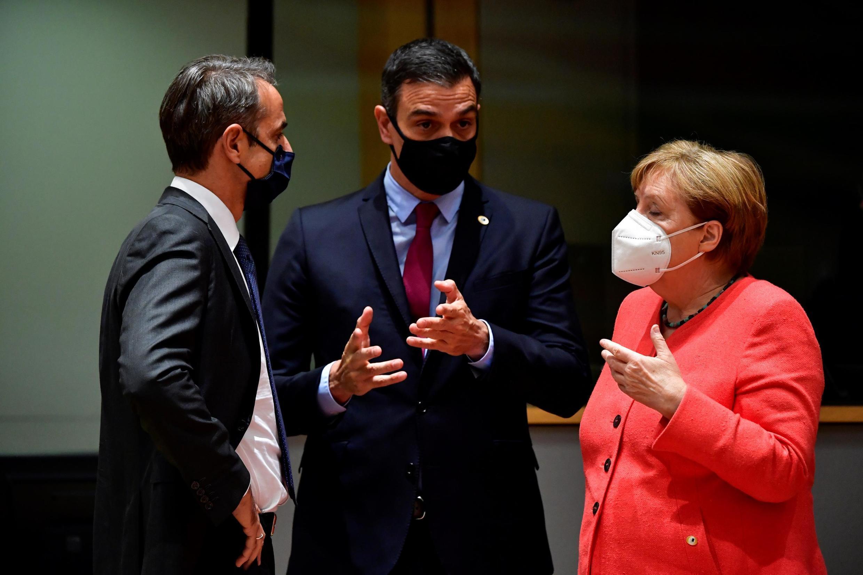 O primeiro-ministro grego, Kyriakos Mitsotakis (à esquerda), conversa com o primeiro-ministro espanhol, Pedro Sanchez (centro), e a chanceler alemã, Angela Merkel, durante a cúpula da UE encerrada nesta madrugada em Bruxelas.