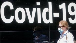 7月22日,纽约市一女子走过一辆新冠检测流动卡车