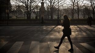 A woman crosses a street in front of the Tuileries Gardens in Paris