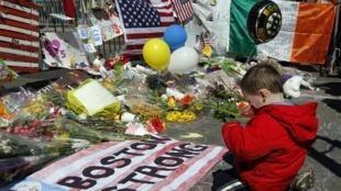 Un jeune enfant devant un momerial pour les victimes de l'attentat lors du marathon de Boston, le 15 avril 2013.