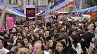 Members of Paris' Chinese community take part in the demonstration in the Belleville district in Paris