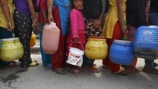 尼泊尔灾民排队领取水。