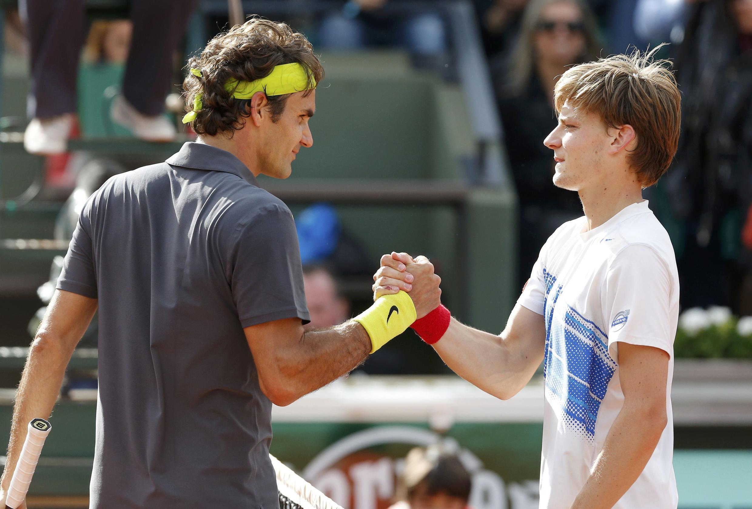 Roger Federer of Switzerland (L) shakes hands with David Goffin of Belgium after winning his match during the French Open