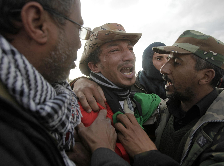 Un opositor libio llora la muerte de un compañero en Ras Lanuf.