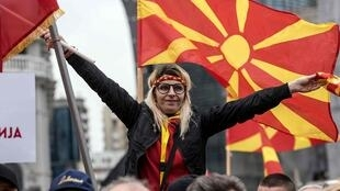 People wave Macedonian flags during a protest in a central square in Skopje on March 4, 2018