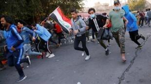 Les manifestants se mettent à l'abri alors que des tirs résonnent dans le ciel de Bagdad, le 31 janvier 2020.