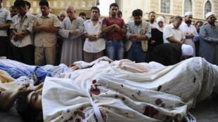 População reza diante de corpos de opositores mortos em confrontos com as forças do regime, em 1 de agosto.