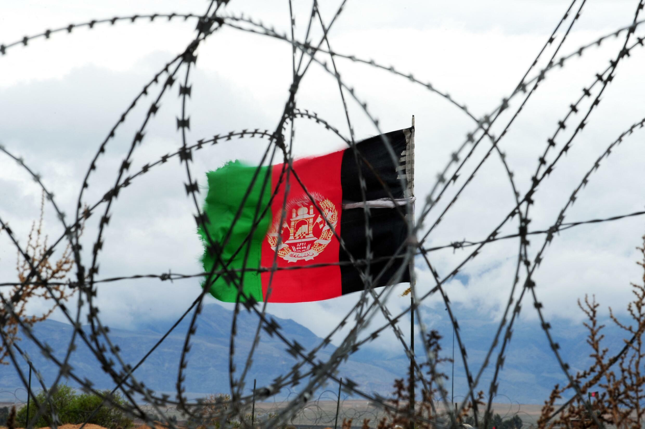 Afghanistan's flag near barbed wire outside of Kabul (illustration) overrun by the Taliban on 15 August 2021.